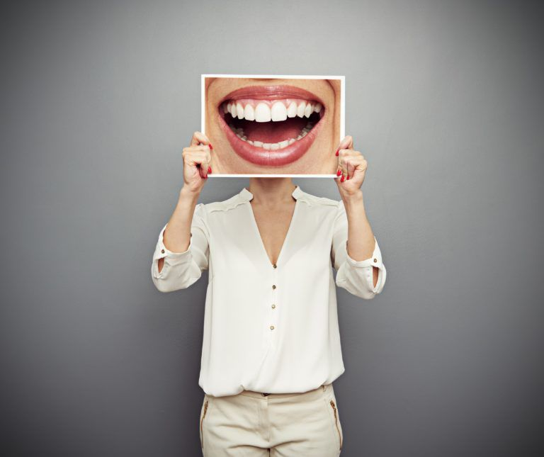 female body holding up a enlarged image of a smile over her face so that it covers her face and all you see in the giant smile