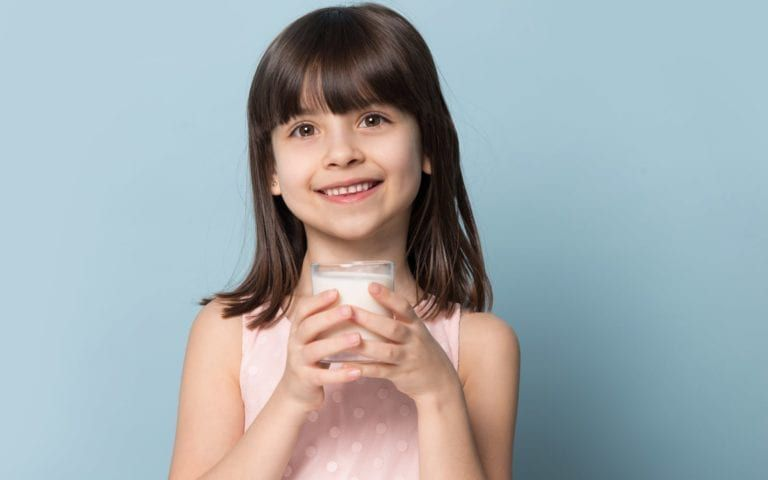 Child drinking milk with a smile