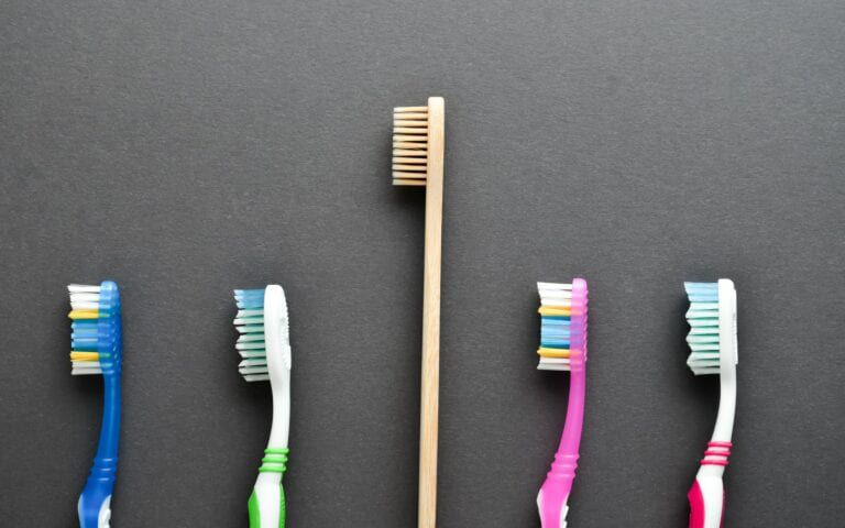 A bamboo toothbrush with plastic toothbrushes